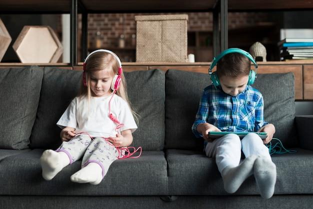 Garçon et fille sur le canapé avec des comprimés