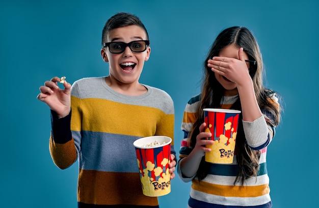Un garçon et une fille choqués mangent du pop-corn dans des lunettes 3d en regardant un film effrayant isolé sur un bleu.