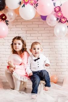 Garçon et fille avec des couronnes sous un ballon d'anniversaire et des décorations en arc de fleurs en papier. photozone enfantine pour la fête