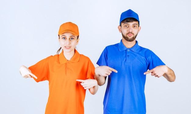 Garçon et fille de courrier en uniformes bleus et jaunes se pointant et se sentant émotif.