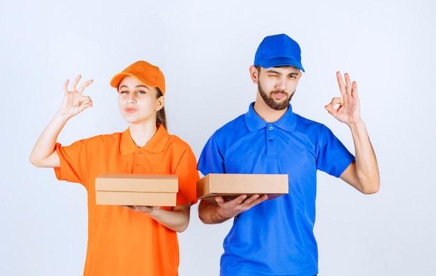 Garçon et fille de courrier en uniformes bleus et jaunes tenant des boîtes à emporter en carton et des colis d'achat et montrant le signe de la main de satisfaction.