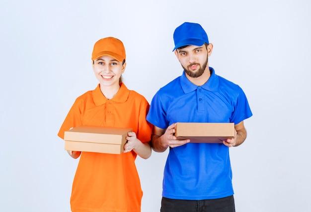 Garçon et fille de courrier en uniformes bleus et jaunes tenant des boîtes à emporter en carton et des colis commerciaux.