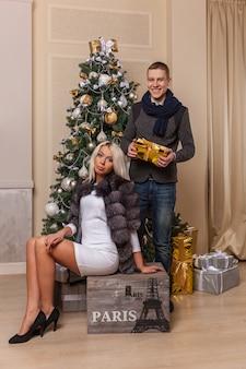 Garçon et fille dans la nouvelle annéebelle fille en robe et chaussures est assise sur la boîte et pose un