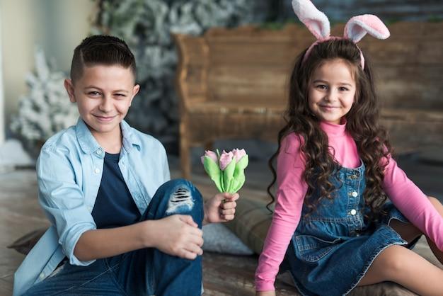 Garçon et fille dans des oreilles de lapin avec des tulipes