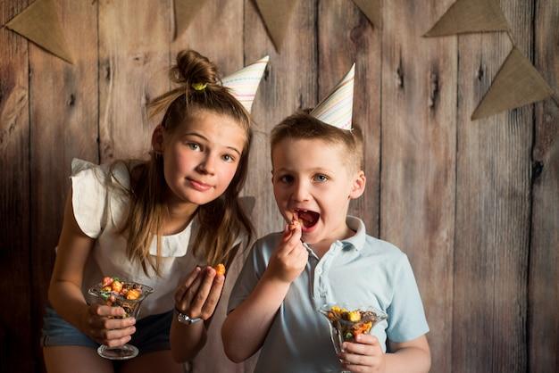 Un garçon et une fille drôles mangeant du maïs soufflé, riant lors d'une fête. fond en bois avec des drapeaux, fête d'anniversaire joyeuse