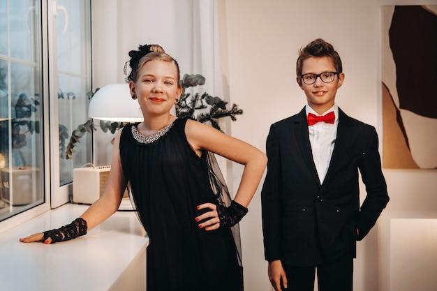 Un garçon et une fille élégants et élégants se tiennent à la fenêtre à l'intérieur de la maison.
