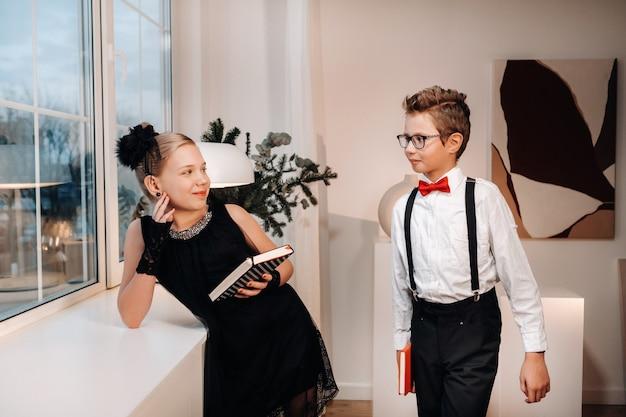 Garçon et fille élégants se tiennent près de la fenêtre avec des livres à la main.