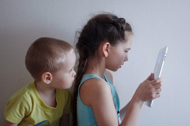 Le garçon et la fille d'enfant en bas âge avec de longues tresses regardent le smartphone