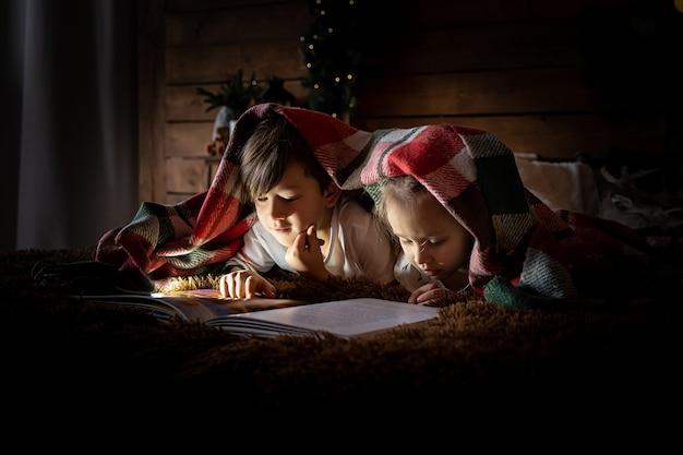 Garçon et fille d'enfants lisent un livre sur un lit près de l'arbre de noël