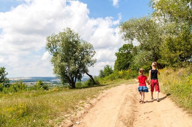 Un garçon et une fille enfants marchent sur un chemin de terre