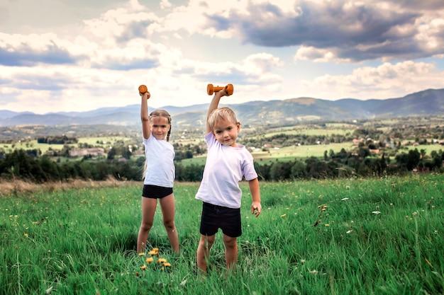 Garçon et fille faisant les exercices du matin avec haltère au sommet des montagnes en été