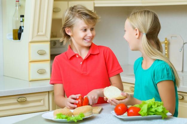 Garçon et fille faisant des hamburgers faits maison