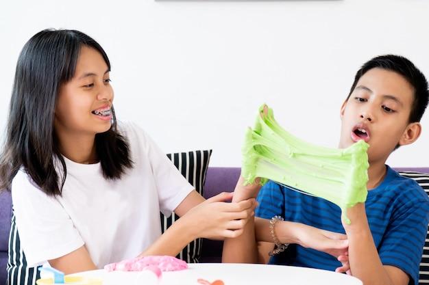 Garçon et fille frères et sœurs main tenant jouet fait maison appelé slime