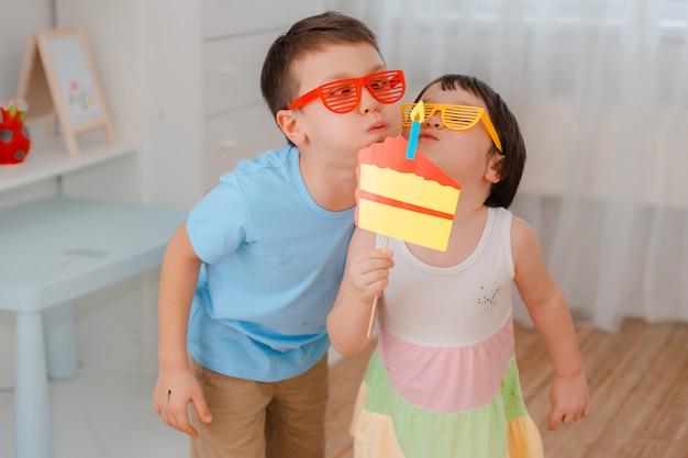 Garçon et fille jouant avec des accessoires papier gâteau avec une bougie.