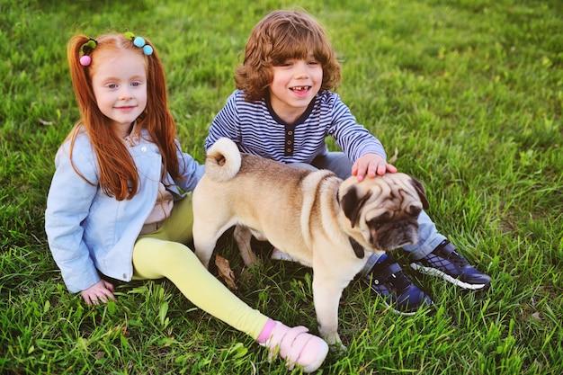 Garçon et fille jouant dans le parc sur l'herbe avec chien de race carlin.