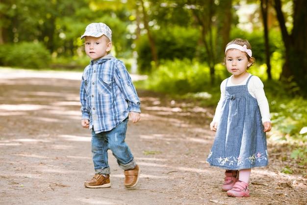 Le garçon et la fille jouent au parc de victoire en plein air