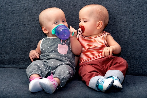 Garçon et fille jusqu'à l'année boivent de l'eau d'une bouteille posée sur le canapé. le concept de jumeaux dans la famille.