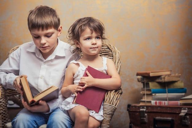 Garçon et fille mignons de bébés dans une chaise lisant un livre dans un intérieur de cru