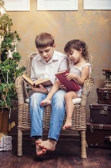 Garçon et fille mignons de bébés dans une chaise lisant un livre dans un intérieur rétro de noël