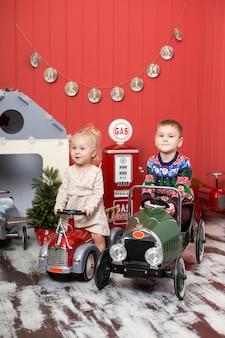 Un garçon et une fille mignons jouent et montent sur des autos miniatures. enfance heureuse