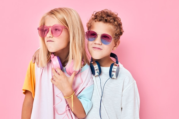 Un garçon et une fille à la mode en lunettes de soleil s'amusent avec des amis à la mode décontractée pour enfants