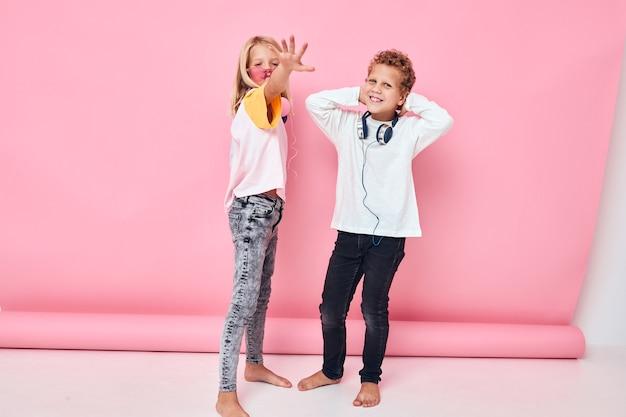 Garçon et fille à la mode portant des écouteurs posant le concept de mode de vie de l'enfance