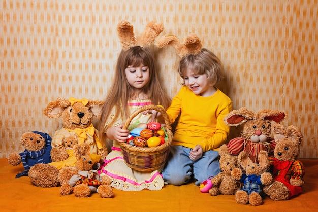 Garçon et fille avec des oreilles de lapin assis autour de beaucoup de paille et de lièvres en peluche, style vintage.