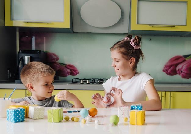 Un garçon et une fille peignent des œufs de pâques assis à la maison dans la cuisine. préparer les vacances de pâques