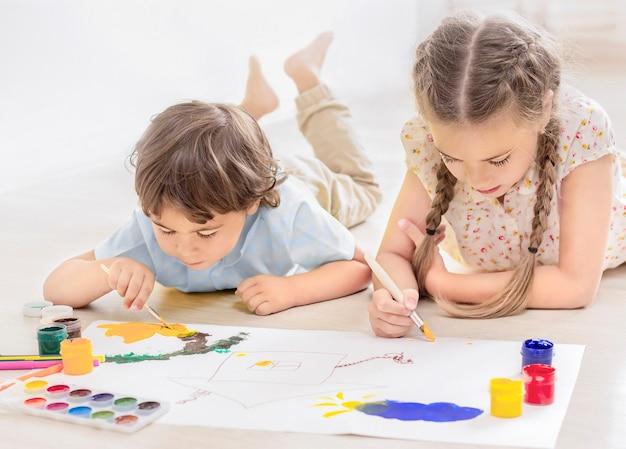 Garçon et fille peignent avec des peintures allongées sur le sol en gros plan