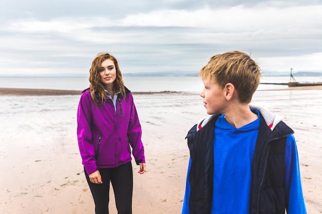 Garçon et fille à la plage un jour de pluie