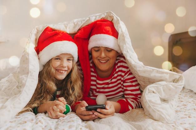 Un garçon et une fille portant des chapeaux de noël sont allongés sous les couvertures avec des smartphones à la main. nouvel an et noël