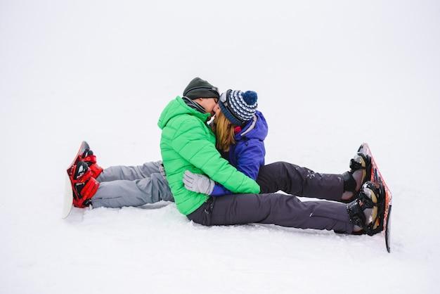 Garçon et fille s'embrasser assis sur la neige