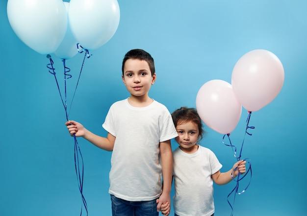 Garçon et fille se tiennent côte à côte se tenant la main et des ballons roses et bleus colorés dans l'autre main sur une surface bleue avec espace de copie