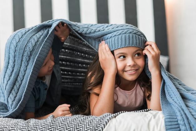 Garçon et fille se trouvant sous la couverture tissée sur le lit