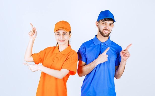 Garçon et fille en uniformes bleus et jaunes montrant quelque chose ci-dessus.