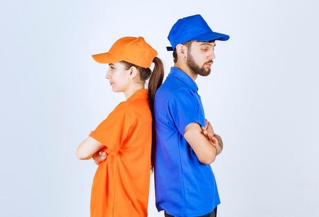 Garçon et fille en uniformes bleus et jaunes se penchant les uns les autres.