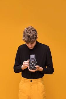Garçon filme avec un caméscope dans une scène jaune