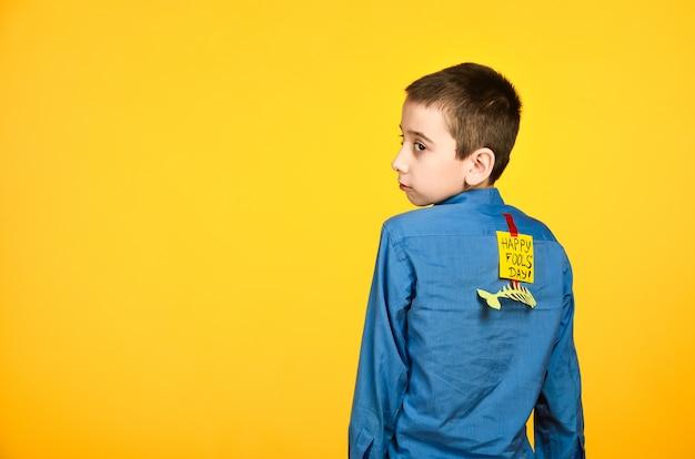 Le garçon sur fond jaune dans une chemise bleue avec un ruban adhésif et un morceau de papier sur le dos