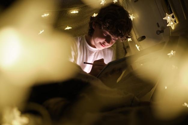 Garçon gai dessinant dans le fort de couverture avec des lampes rougeoyantes