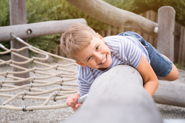Garçon gai et espiègle s'amusant sur une aire de jeux en bois à l'extérieur.