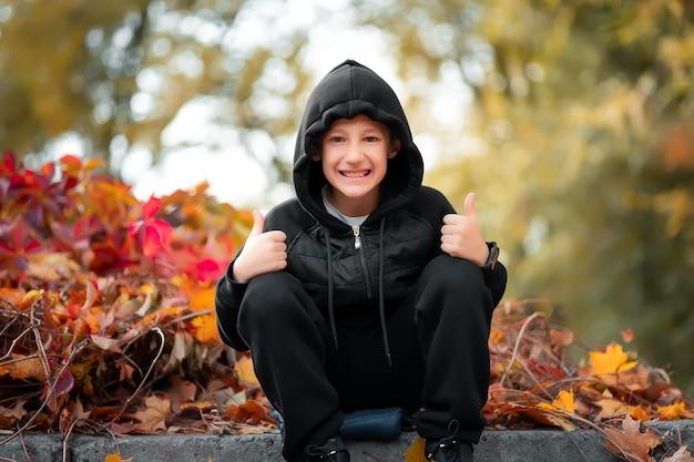 Un garçon gai portant des vêtements noirs est assis à la frontière dans le contexte d'un buisson d'automne et montre des gestes