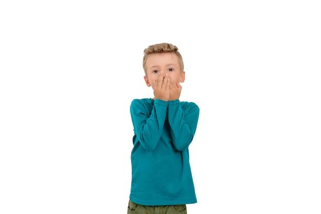Un garçon avec des gestes de la main montre son inquiétude ou devine ou essaie de dissimuler l'odeur de sa bouche