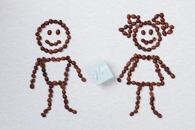Garçon de grain de café symbolique donnant un cadeau à sa petite amie. surface isolée blanche.