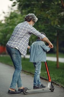 Garçon et grand-père marchent dans le parc. vieil homme jouant avec son petit-fils. enfant avec scooter.
