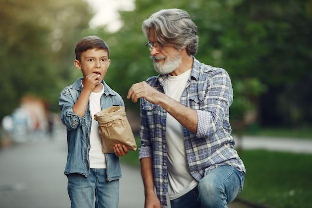 Garçon et grand-père marchent dans le parc. vieil homme jouant avec son petit-fils. les gens mangent du pop-corn.