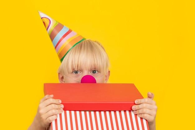 Garçon habillé en clown ouvre la boîte-cadeau. boîte avec surprise. fête des enfants.