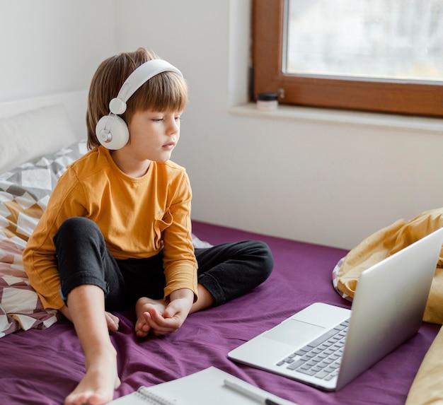 Garçon de haute vue assis dans son lit et apprentissage