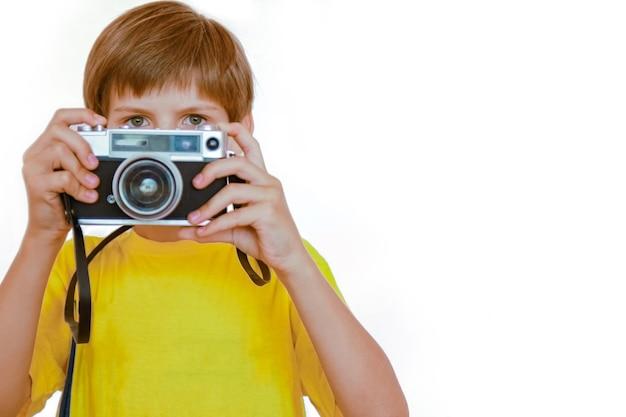 Garçon heureux avec un appareil photo sur le mur