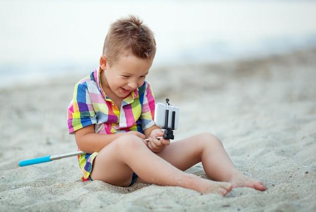 Garçon heureux avec bâton de selfie et cellule au bord de la mer