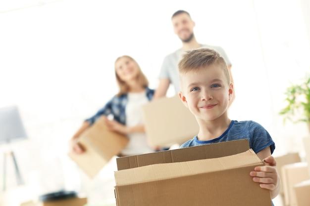 Garçon heureux avec boîte sur floue. concept de déménagement